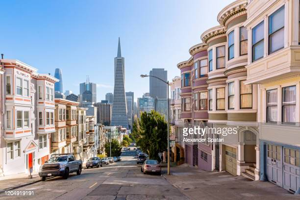 street with residential district with skyscrapers of san francisco financial district in the background, san francisco, california, usa - san francisco california stock pictures, royalty-free photos & images