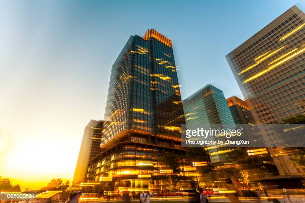street with shopping malls and skyscrapers in marunouchi otemachi district in tokyo, japan at sunset. - only japanese stock pictures, royalty-free photos & images