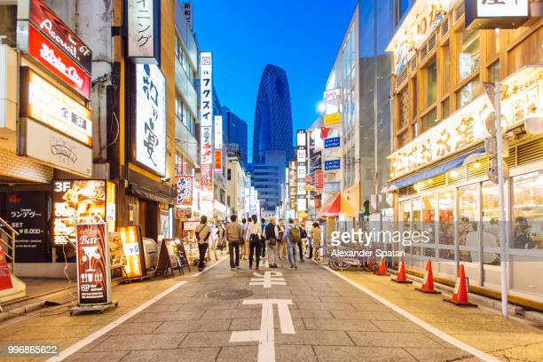 street with shops and restaurants in shinjuku district in tokyo, japan - japón fotografías e imágenes de stock