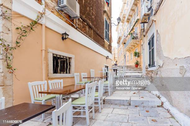 street with sidewalk cafe in corfu town, corfu island, greece - corfu stock pictures, royalty-free photos & images