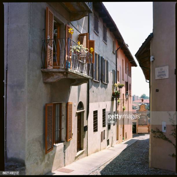 street with small windmills of old saluzzo city, italy - saluzzo stock photos and pictures