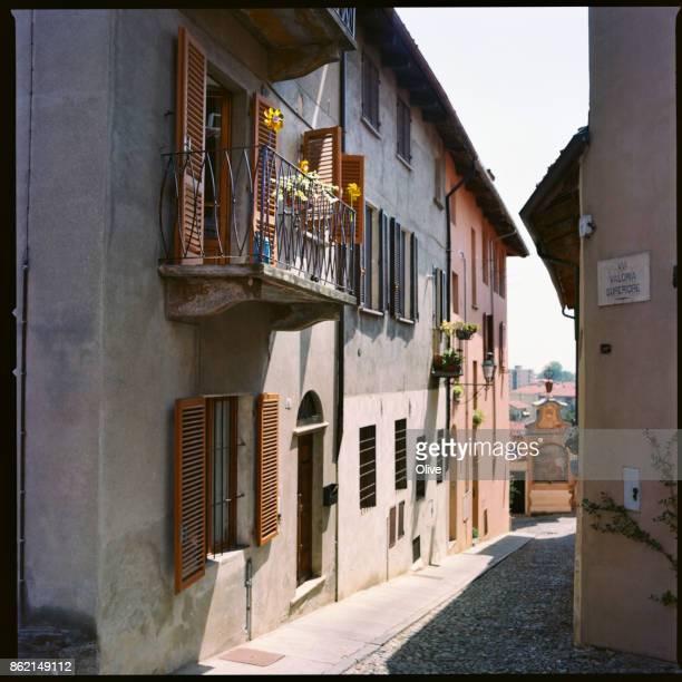 street with small windmills of old saluzzo city, italy - saluzzo fotografías e imágenes de stock