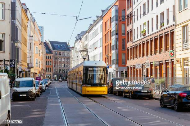 street with yellow cable car on a sunny day, berlin, germany - kleinstadt stock-fotos und bilder