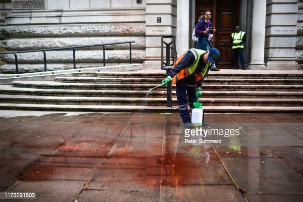 A street worker cleans fake blood from outside the Treasury building on October 3 2019 in London England Climate change activists from the group...