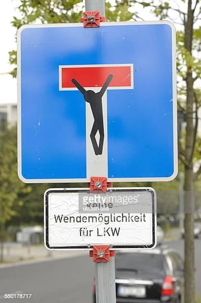 Streetart kurios Gekreuzigter an dem Verkehrsschild Sackgasse in Berlin