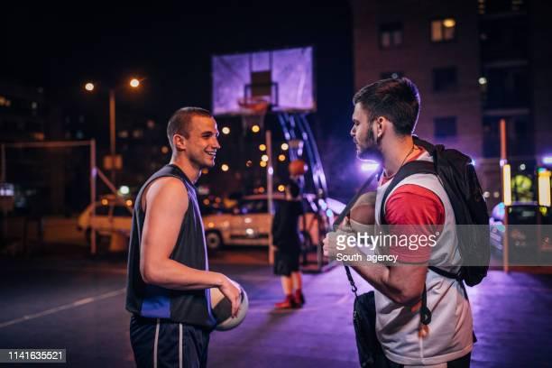 amigos de streetball na corte ao ar livre na noite - basketball hoop - fotografias e filmes do acervo