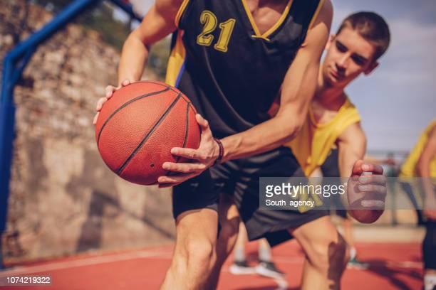 streetball spieler auf platz - basketball stock-fotos und bilder