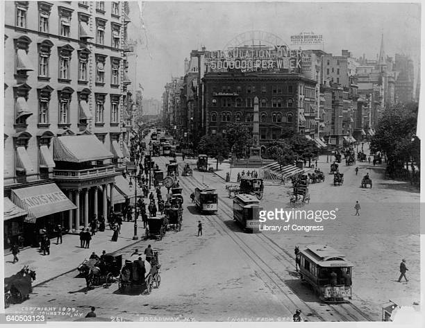 Streetcars pass at the intersection of Broadway and 23rd Street marked by Worth Monument on the corner ca 1899 New York City