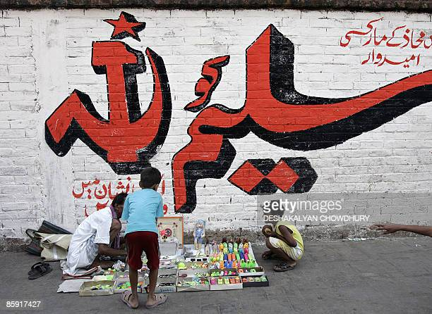 A streetside vendor sells toys on a pavement beside an election campaign mural of the Communist Party of India in Kolkata on April 12 2009 Indian...