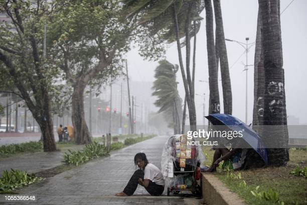 TOPSHOT A streetside vendor shivers in the rain as weather patterns from Typhoon Yutu affect Manila Bay on October 30 2018 Typhoon Yutu slammed into...