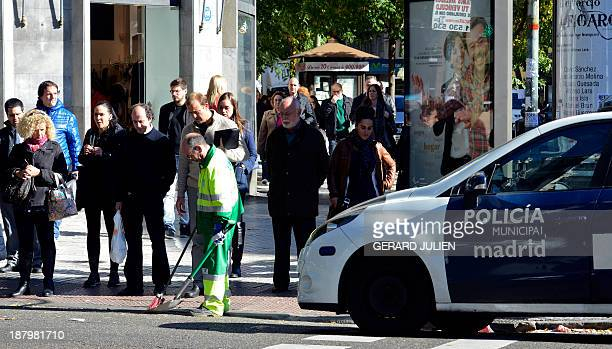 A streetsweeper executes minimum services next to a police car in the Calle Goya in Madrid on November 14 2013 during an openended strike by...