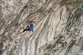 Strenuous male rock climber ascending on craggy rock face