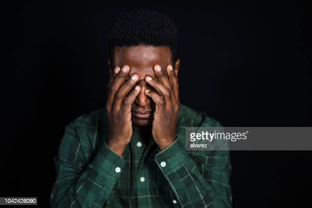 stressed african man on black background - head in hands stock pictures, royalty-free photos & images