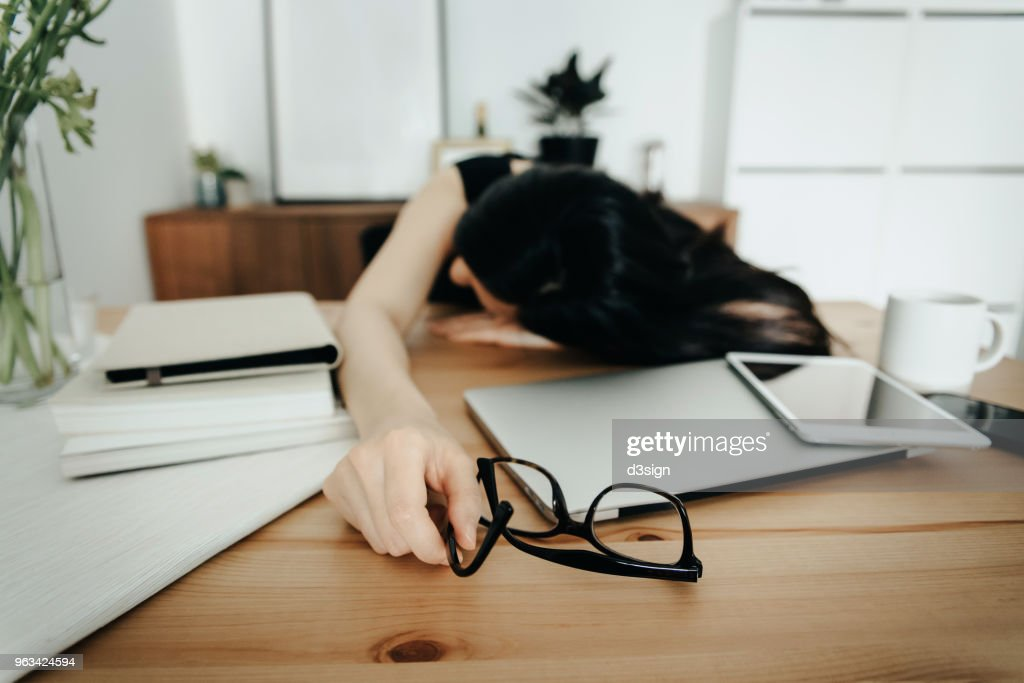 Stressed and overworked businesswoman resting on desk in office : ストックフォト