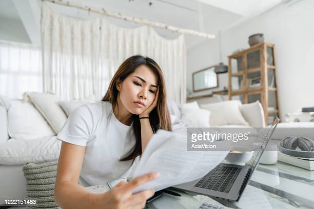 stressed and worried young asian woman working from home, handling paperworks and going through her financials - financial bill stock pictures, royalty-free photos & images