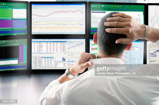Stressed Asian businessman reading charts on computer screen