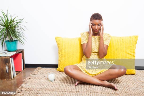 Stressed Black woman meditating on floor