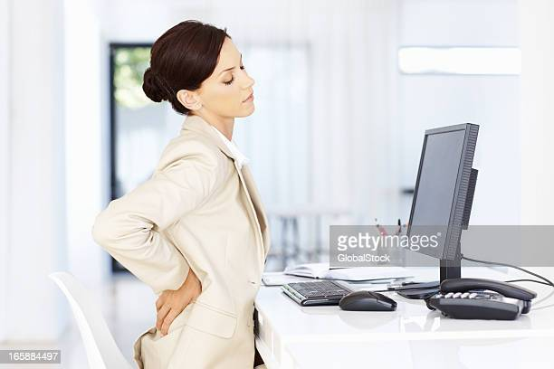 stressed business woman - lower back stock pictures, royalty-free photos & images