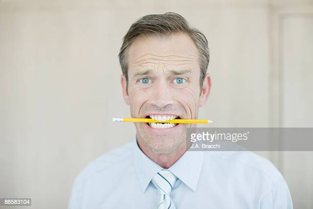 Stressed businessman biting pencil