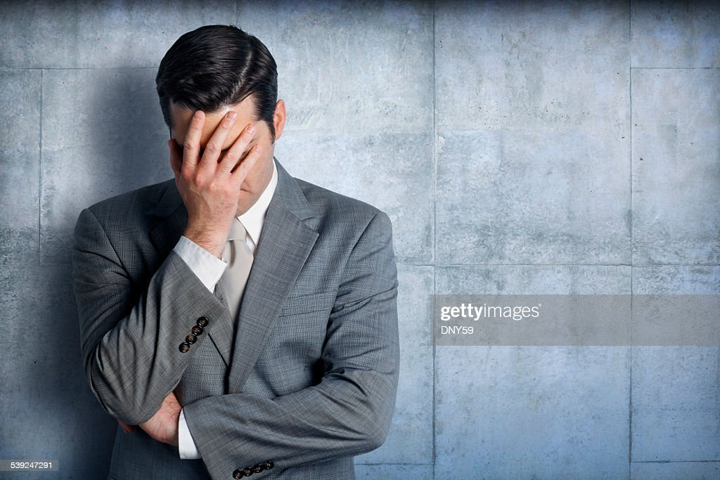 Stressed businessman leaning against concrete wall : Stock Photo