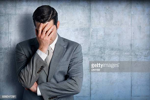 Stressed businessman leaning against concrete wall