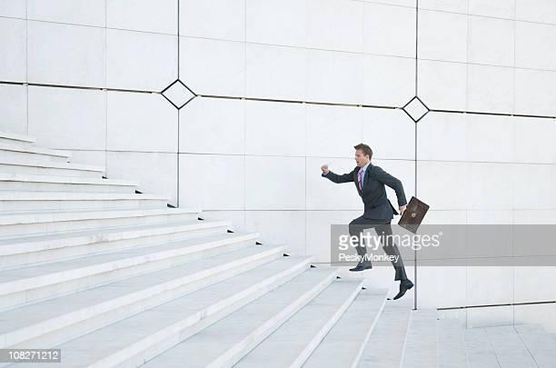Betonte Geschäftsmann läuft bis weißen Treppe im Freien
