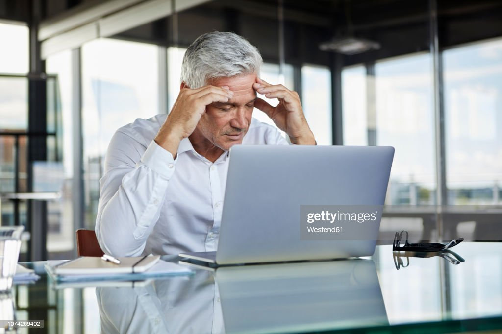 Stressed Businessman Sitting At Desk With Laptop Holding His