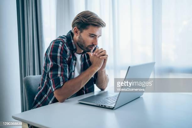 beklemtoonde zakenman die laptop thuis gebruikt. - flexplekken stockfoto's en -beelden