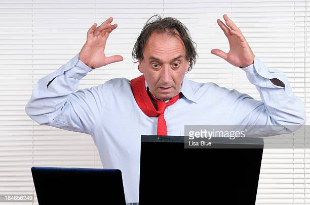 Stressed Businessman with Arms Raised Looking PC
