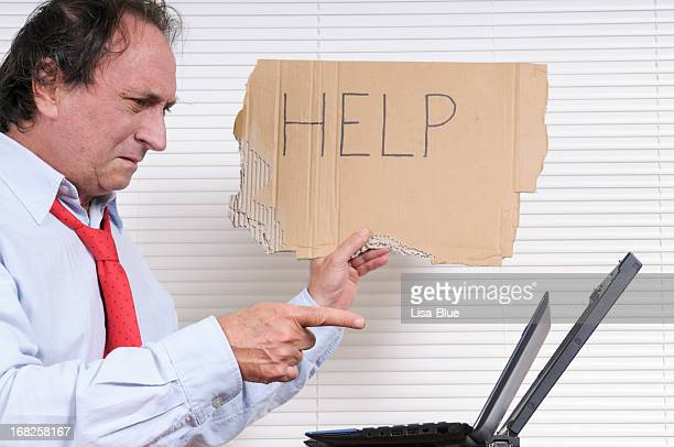 Stressed Businessman with Help Sign Looking PC
