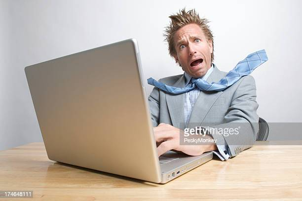 Stressed Businessman Working on Laptop Computer at Desk
