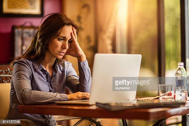 Stressed businesswoman holding head in pain while working on laptop.