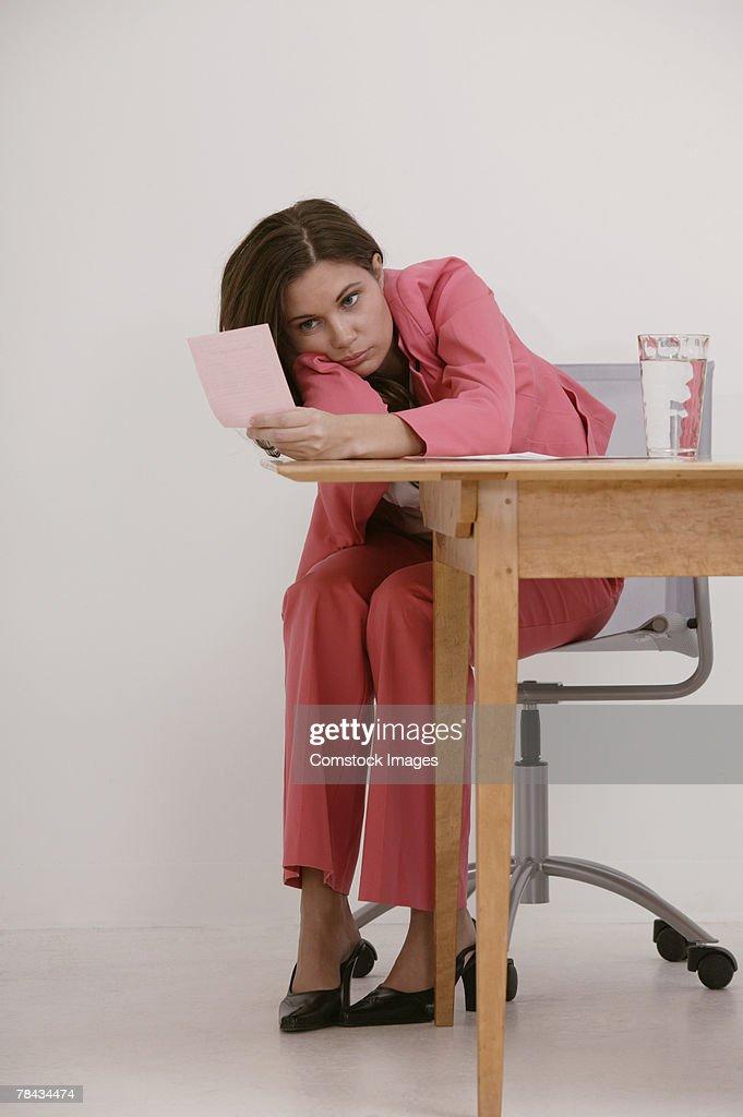 Stressed businesswoman staring at pink slip : Stockfoto