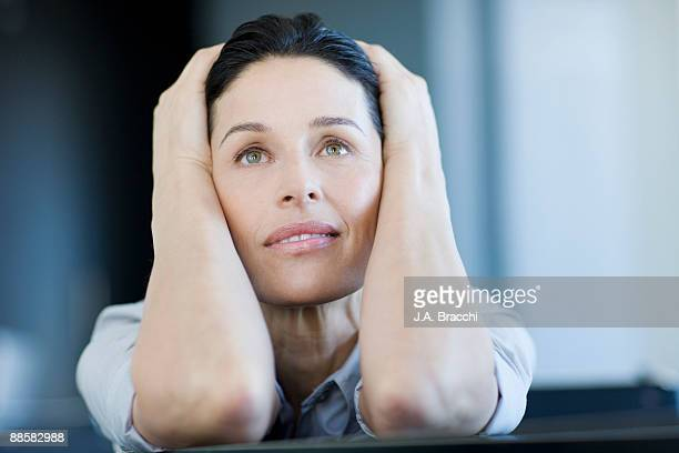 Stressed businesswoman with head in hands