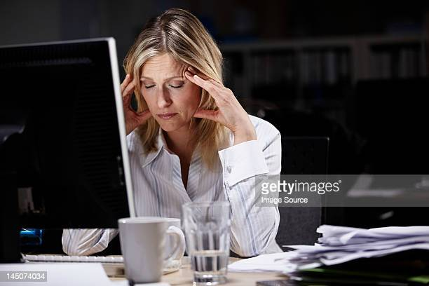 Stressed businesswoman working late