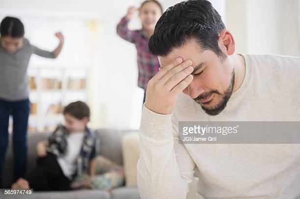 Stressed Caucasian father with shouting children in living room
