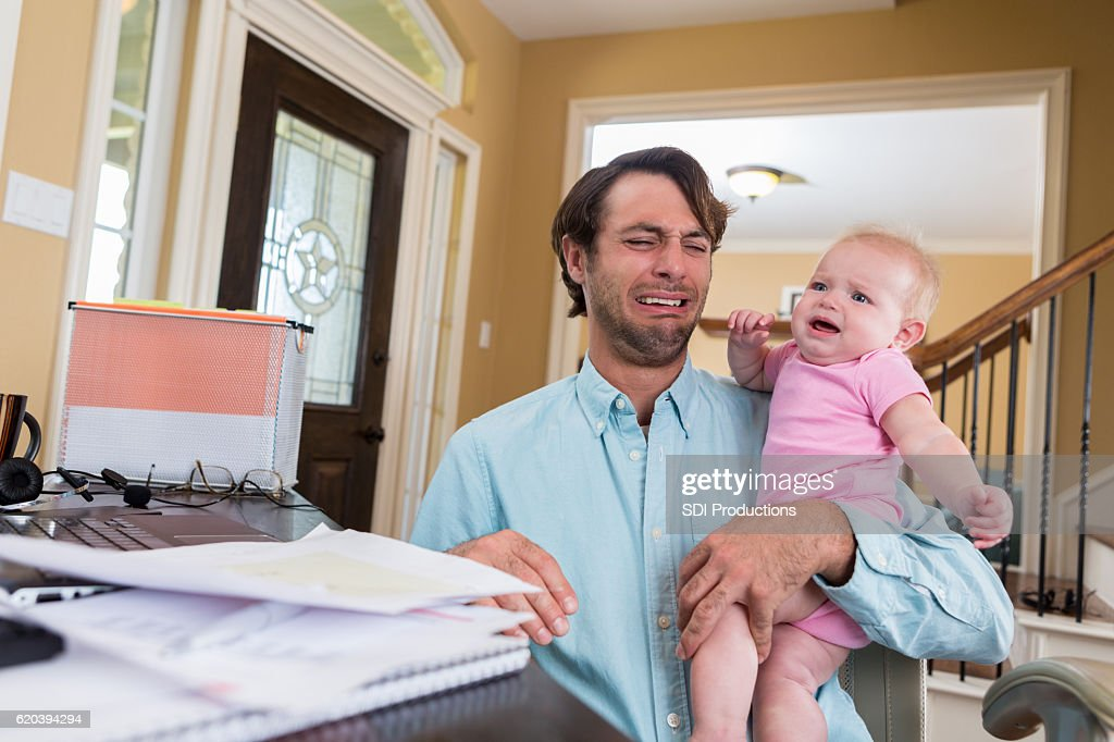 Stressed dad with baby working from home : Stock Photo