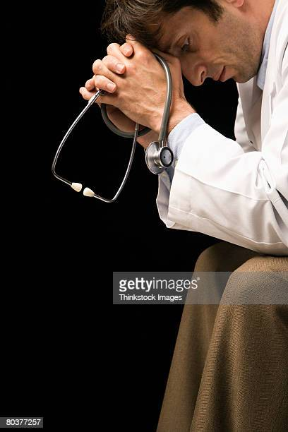 Stressed doctor holding stethoscope