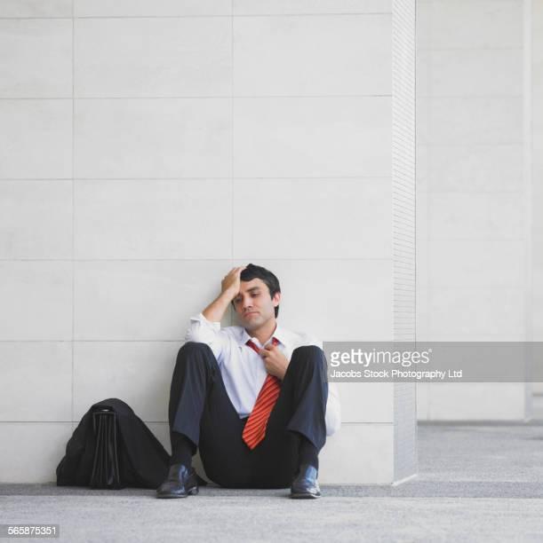stressed hispanic businessman sitting on floor against wall - mid adult men fotografías e imágenes de stock