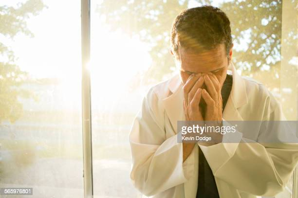 Stressed Hispanic doctor rubbing his eyes