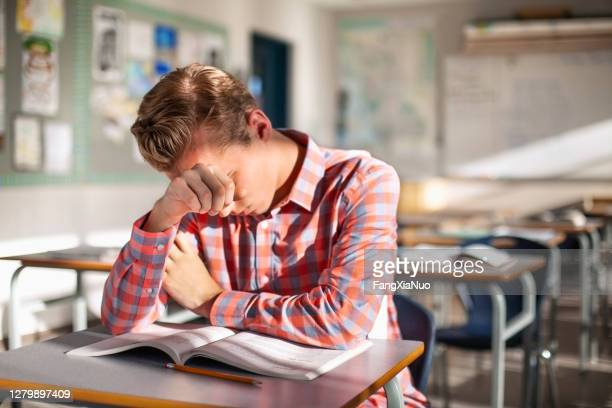 stressed male student sitting with book at desk - struggle stock pictures, royalty-free photos & images