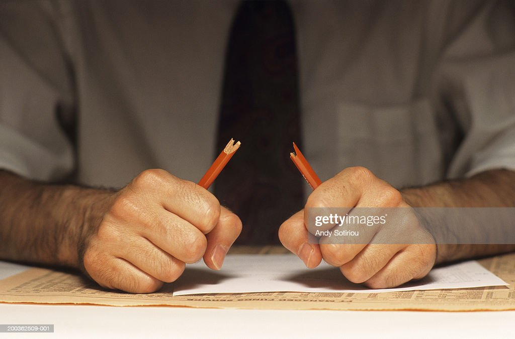 Stressed man breaking pencil, (Mid section) : Stock Photo