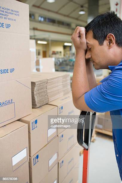 Stressed man by boxes