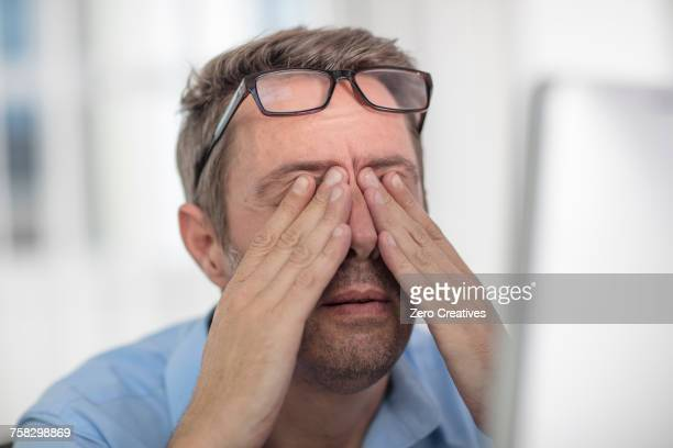 stressed man rubbing eyes - rubbing stock photos and pictures