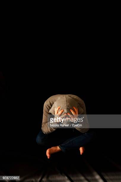Stressed Man Sitting Against Black Background