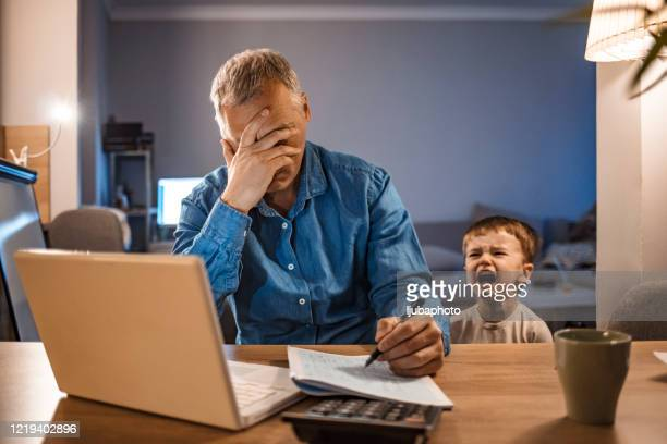 stressed man with his two years old son working from home - parent stock pictures, royalty-free photos & images