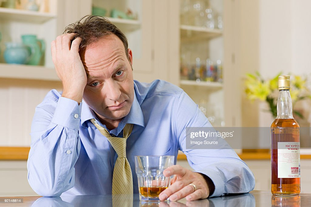 Stressed man with whisky : Stock Photo