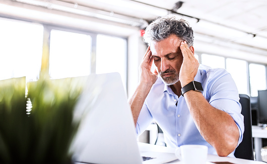 Stressed mature businessman sitting at desk in office with laptop - gettyimageskorea