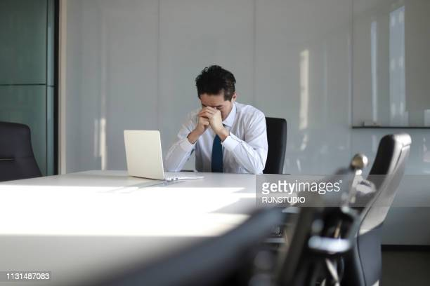 stressed mature businessman with laptop - ongerust stockfoto's en -beelden