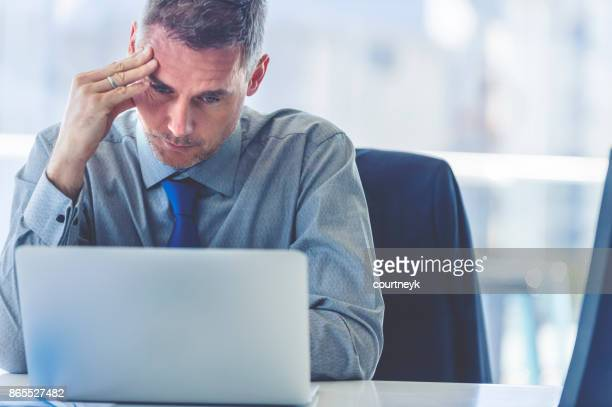 stressed mature businessman with laptop. - crisis stock photos and pictures